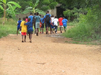RtD players walking through village towards the training pitch